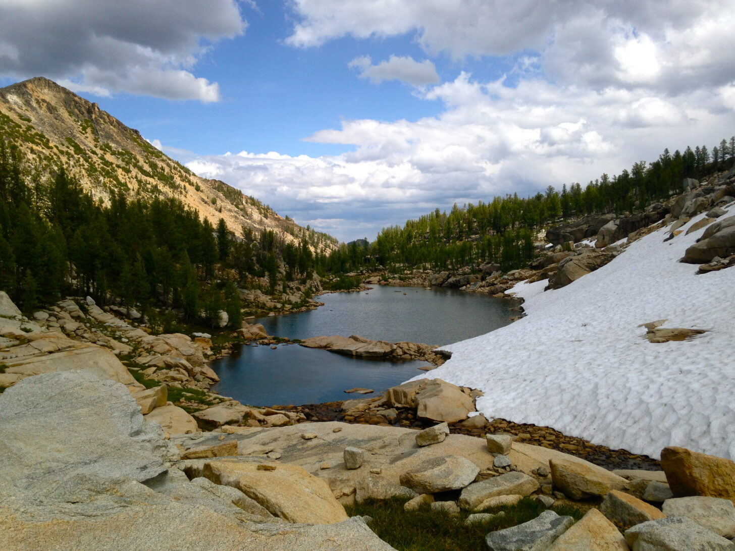 a lake surrounded by snowpack and rocks with a mountain in the background.