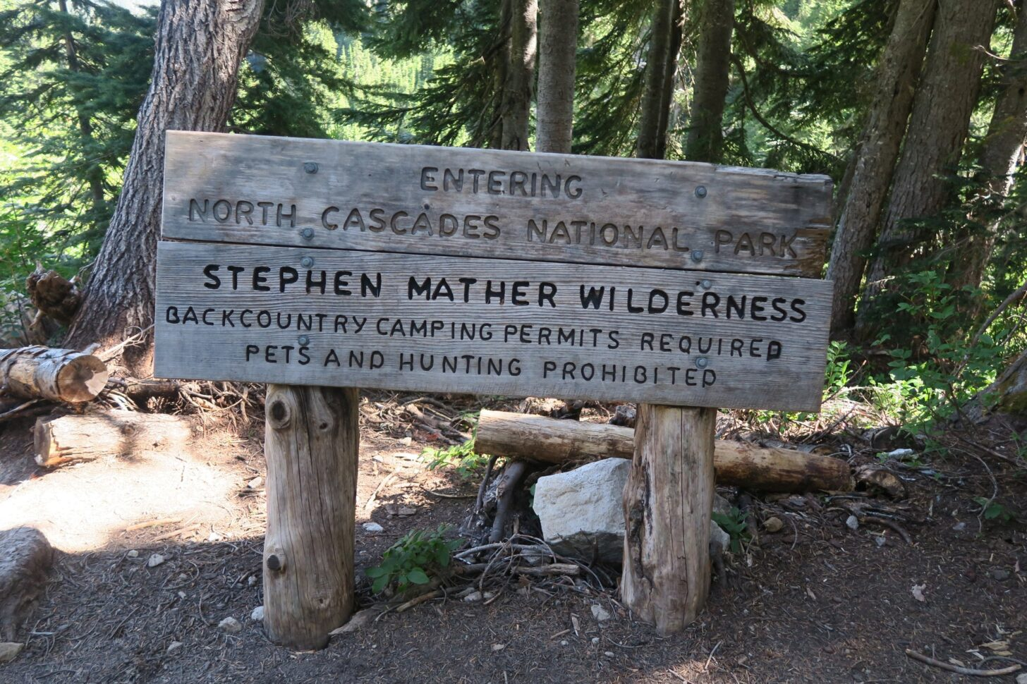 """A sign that reads """"Entering North Cascades National Park, Stephen Mather Wilderness: Backcountry camping permits required, pets and hunting prohibited."""""""