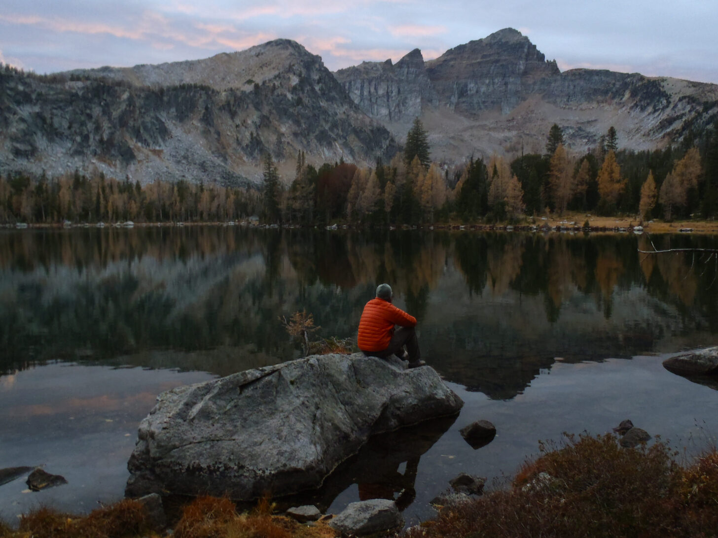 a man sits on a rock overlooking a calm, flat lake with rugged mountains in the distance.