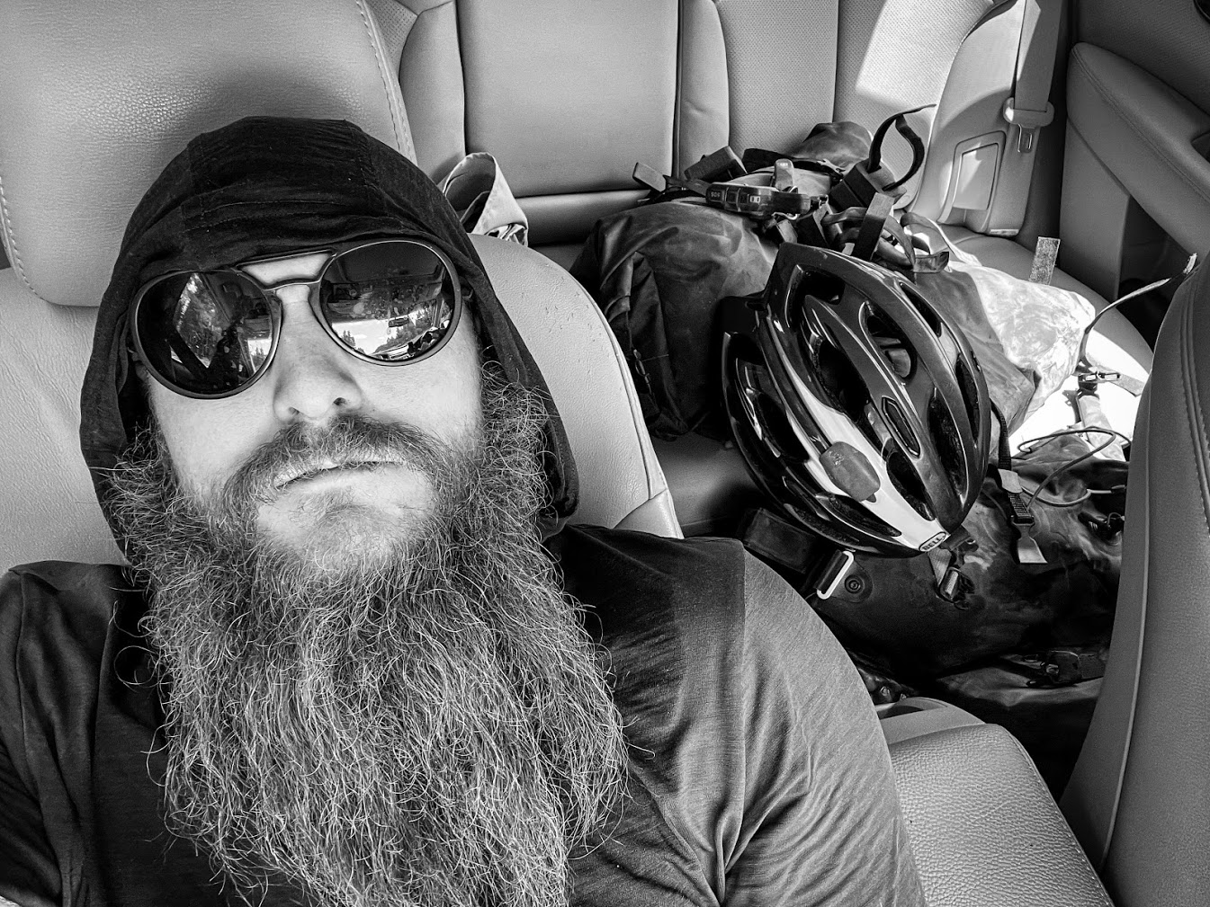 A man with a luxuriously long beard reclines in the front seat of a car with bikepacking gear visible in the back seat.