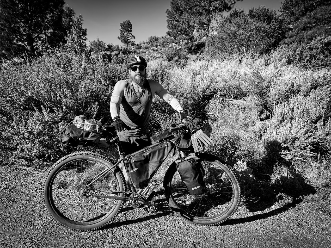 A black and white photo of a man standing next to his bicycle with scrub and trees in the background. The man's luxuriously long beard is braided viking-style.