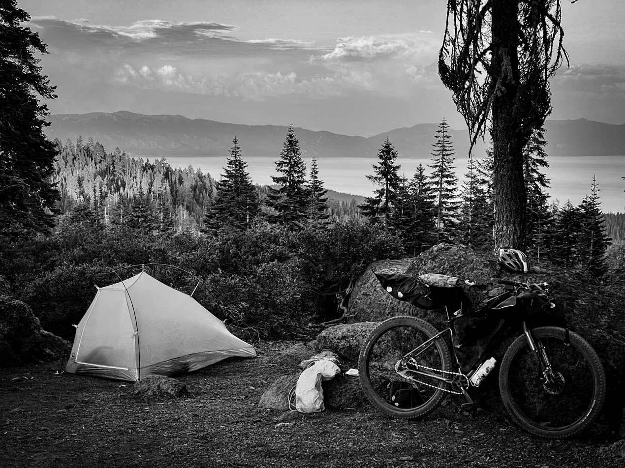 A black and white image of a bicycle and a tent on a ridge above an alpine lake.