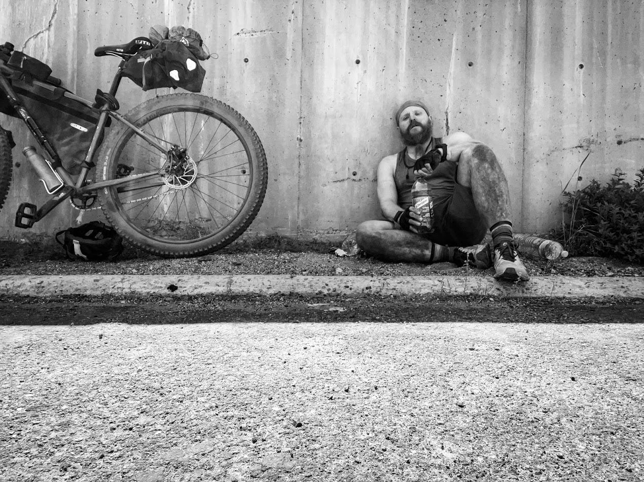 a man leans against a concrete wall with a bike next to him. The man is filthy.