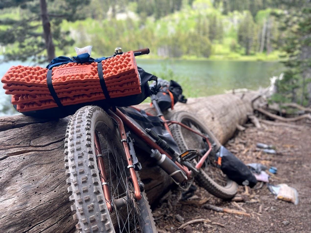 a bikepacking bike leaned up against a log next to an alpine lake.