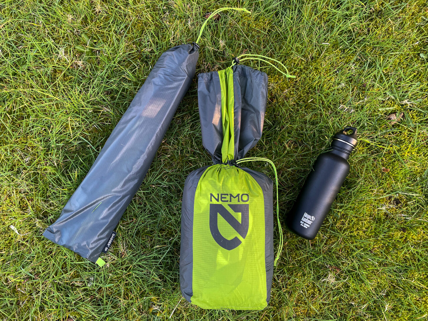 Stuff sack, water bottle, and tent poles divided out on the ground.