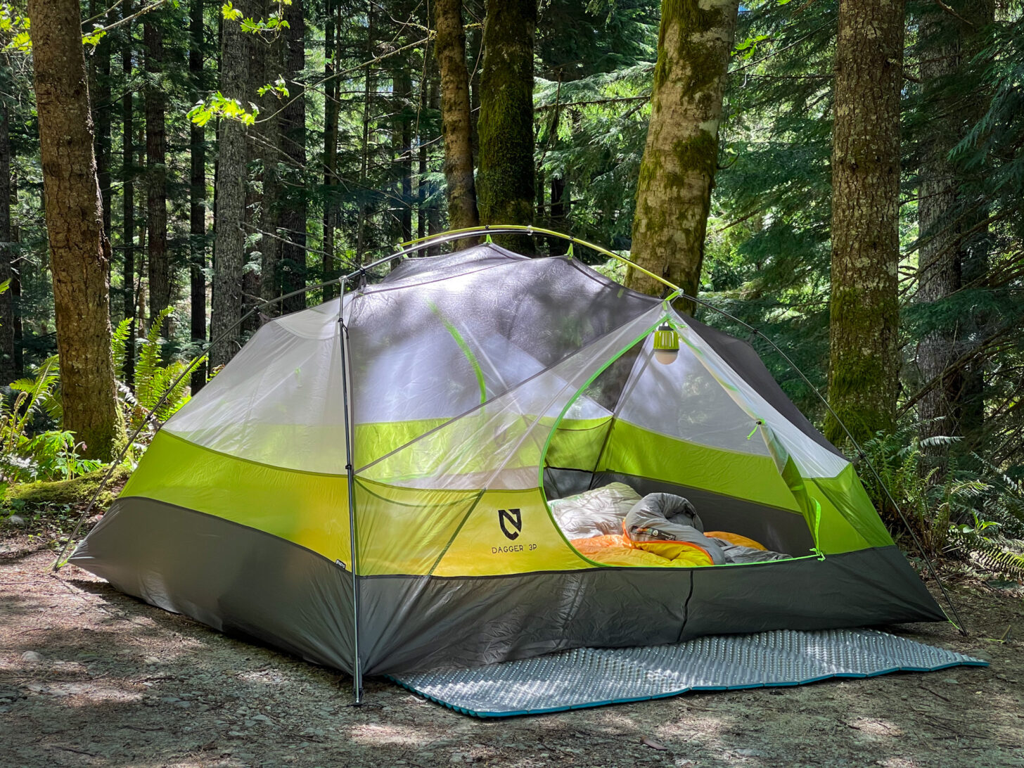 A wide shot of the shelter set up in a lush forest.