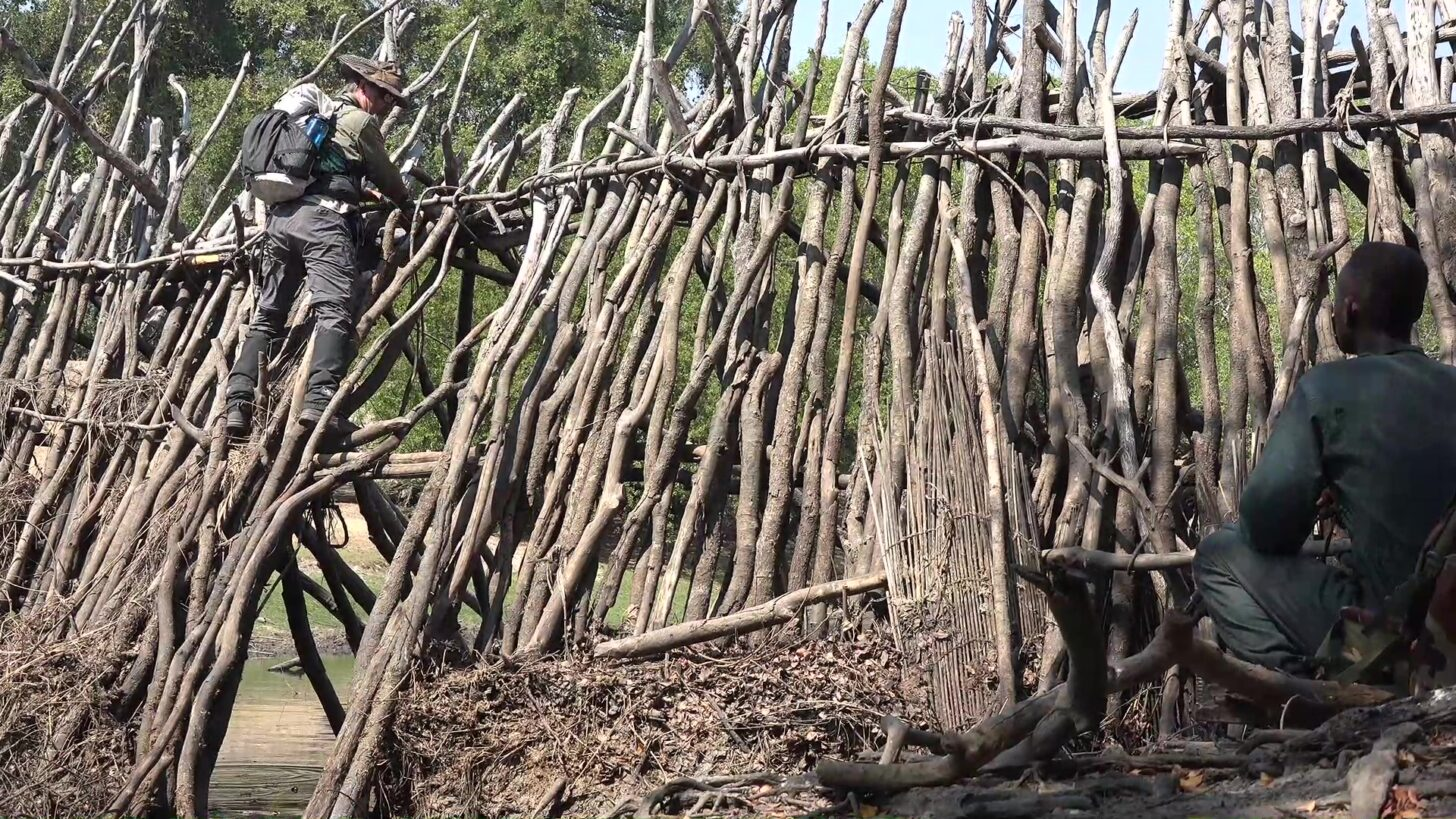 a man picks his way across a rickety wooden damn