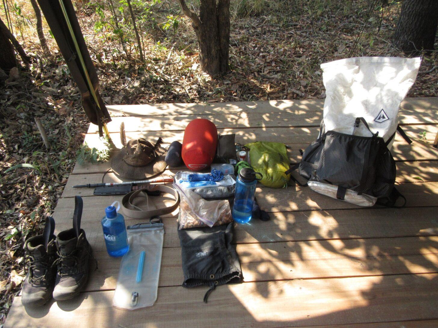lightweight backpacking gear spread out across a wooden deck.