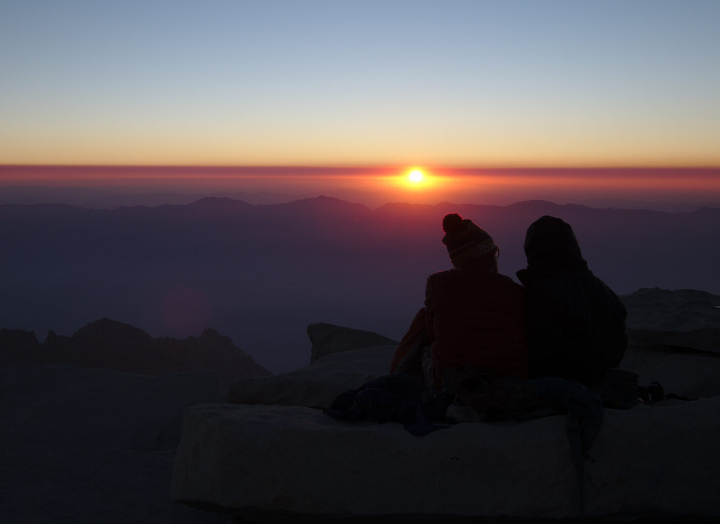 Sun rising through thin clouds over distant mountains, with two hikers silhouetted in the foreground.