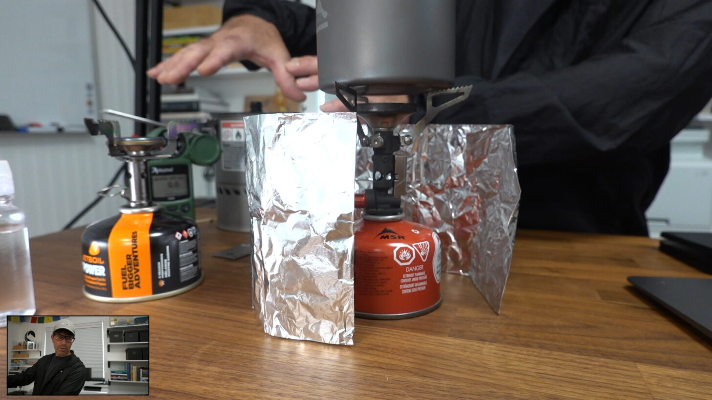 an upright canister stove surrounded by a cheap aluminum foil windscreen