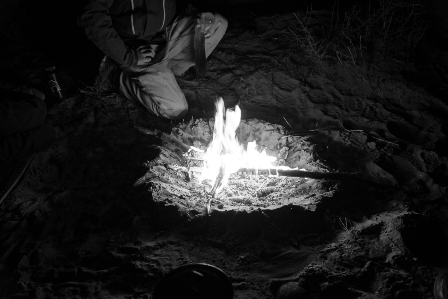 a black and white photo, taken at night. The photo is mostly dark, but the light from the fire is just enough to illuminate a man's knees. The man is kneeling next to the fire.