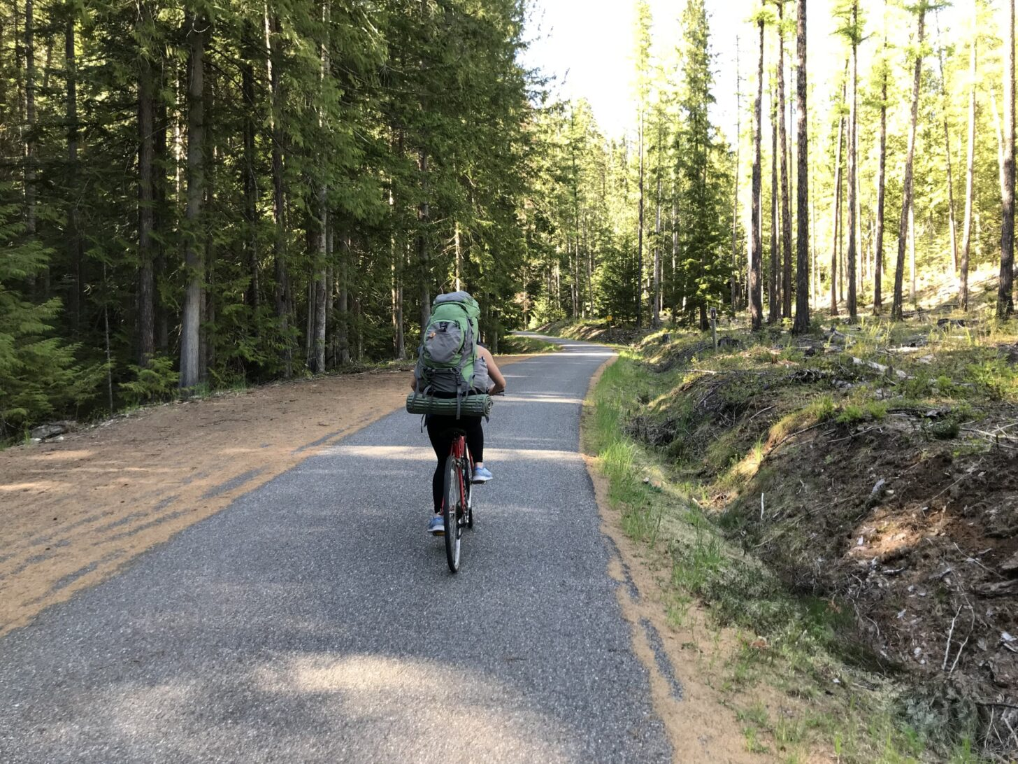 a woman rides a bicycle down a paved path while wearing a backpack