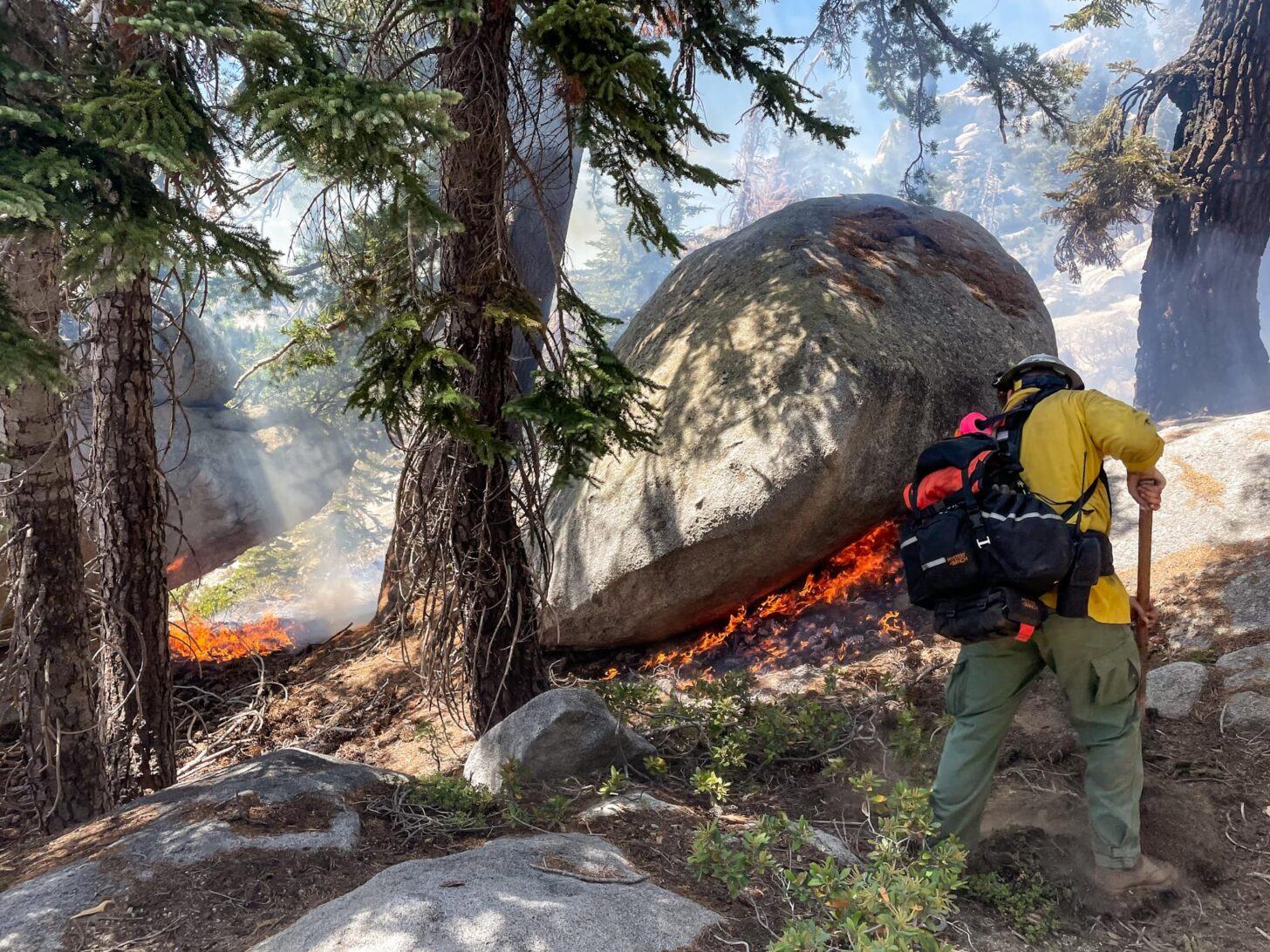 A firefighter wearing a backpack and helmet digs at the ground. Smoke hazes the photo, and flames are visible underneath a boulder in the middleground.