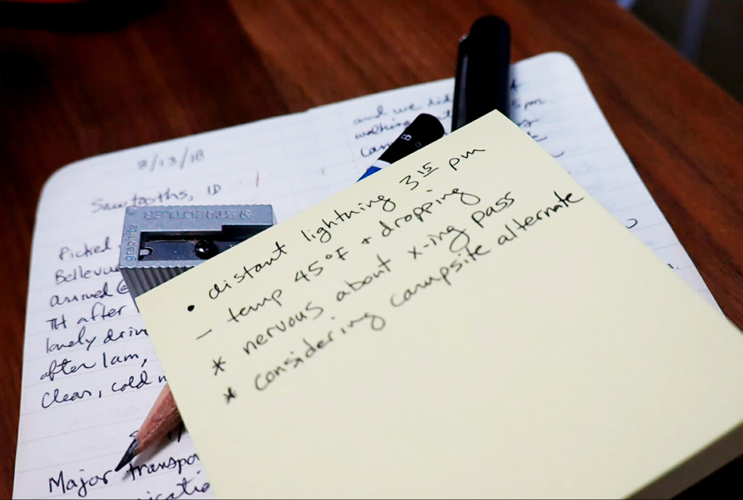 a sticky note sits on top of a pencil, pen, pencil sharpener, and small notebook. On the sticky note are a few bullet points with notes next to them.