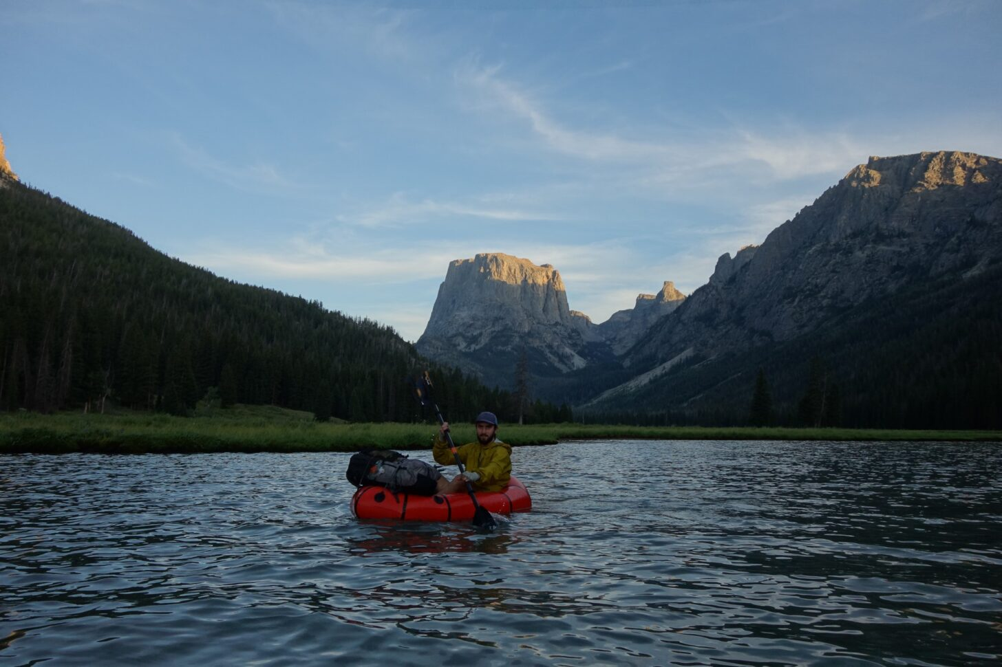 a man floats on a packraft with a squared off mountain behind him in the background