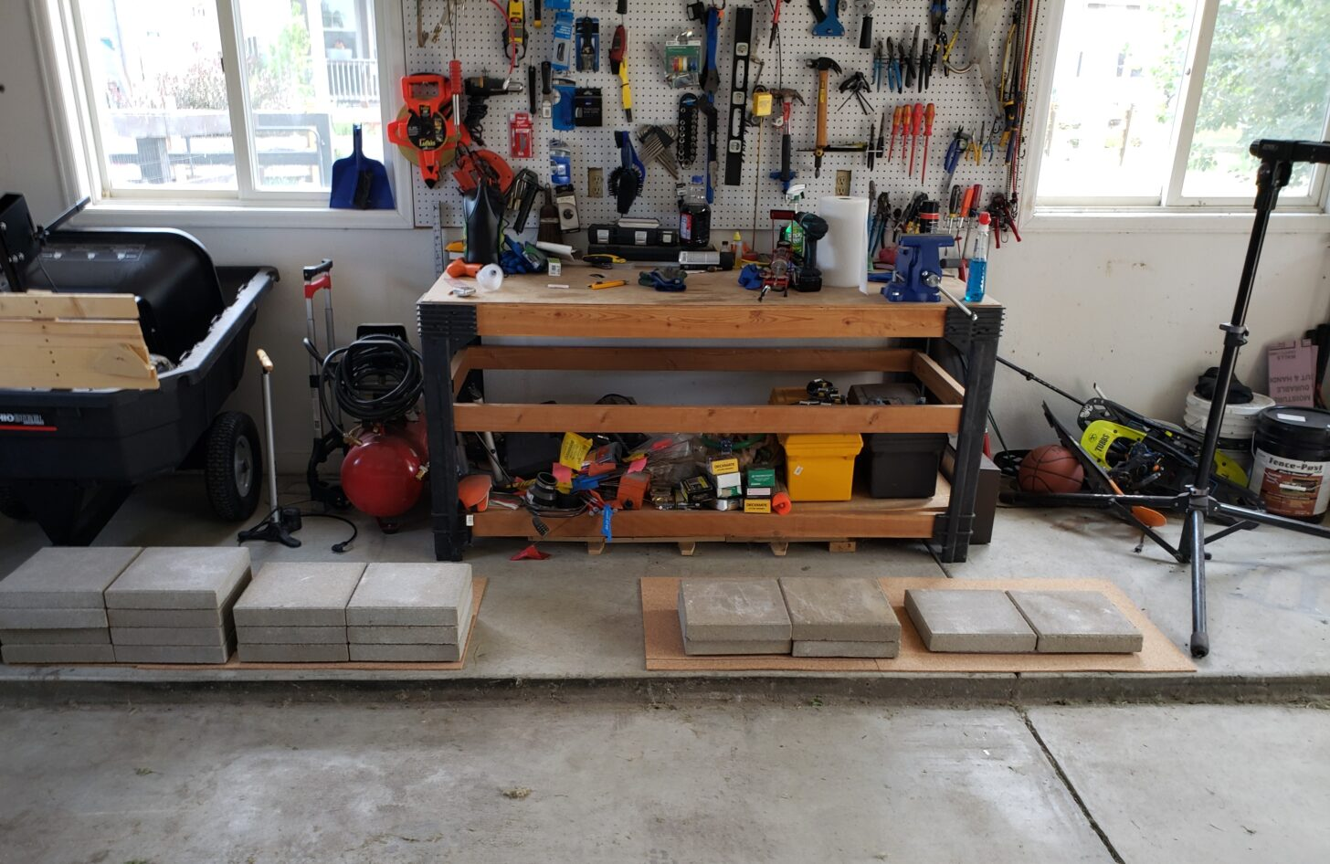 A tidy workshop featuring a rack wall of tools, a workbench, and - on the ground - a row of pavers in increasingly high stacks.