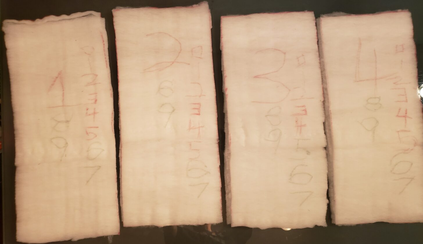 four more samples of insulation aligned side by side against a neutral background. The samples are off-white and shaped like bricks.
