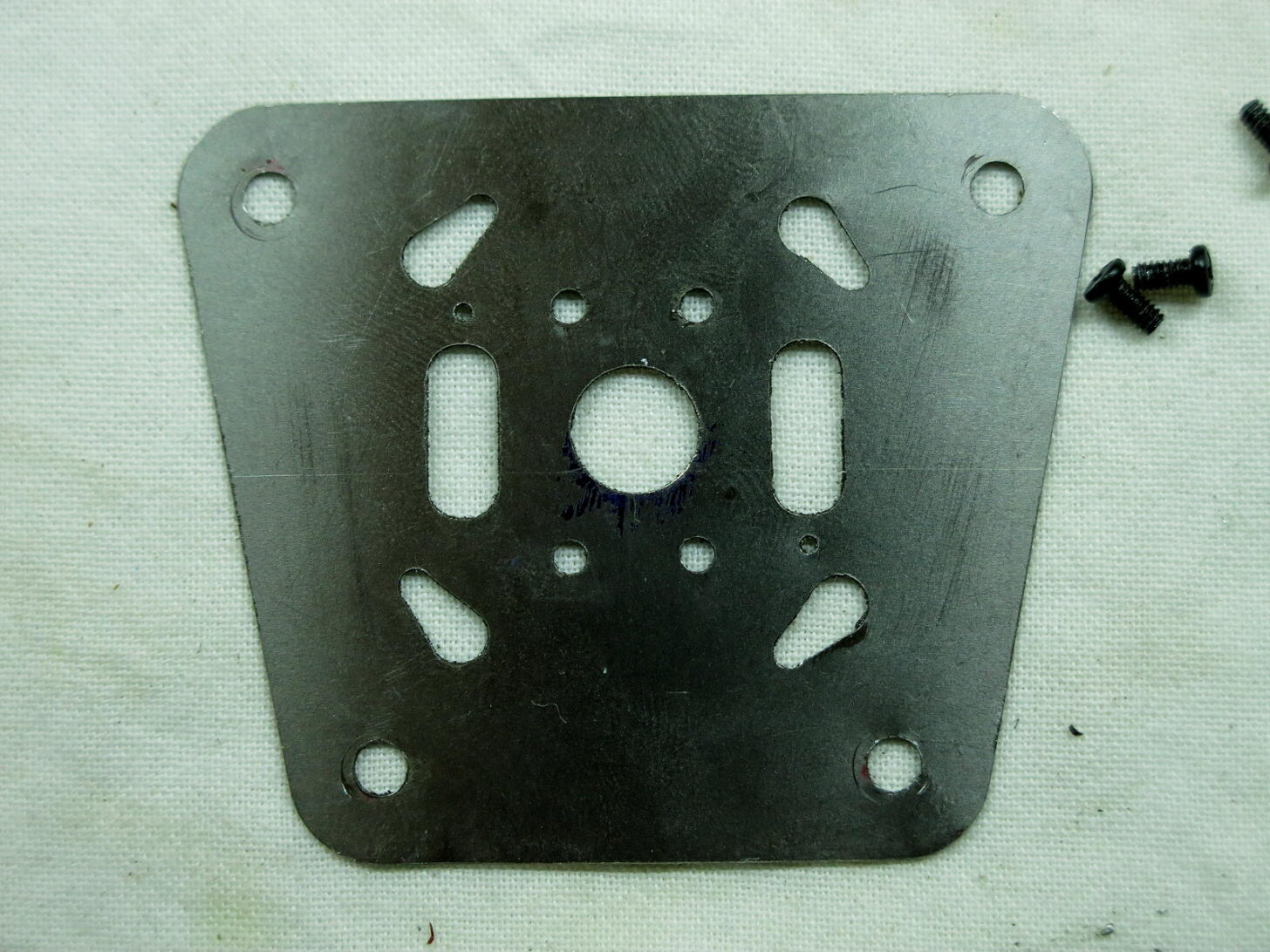 a stove baseplate with holes cut into it and a tapered shape
