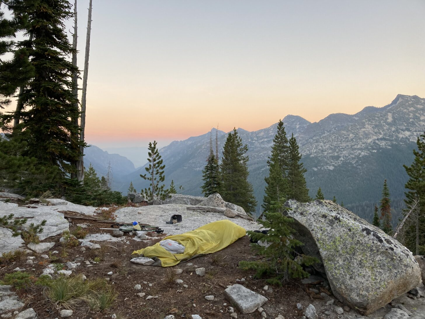 a campsite looking out over a range of mountains and a canyon, with a haze of fog or smoke in the background