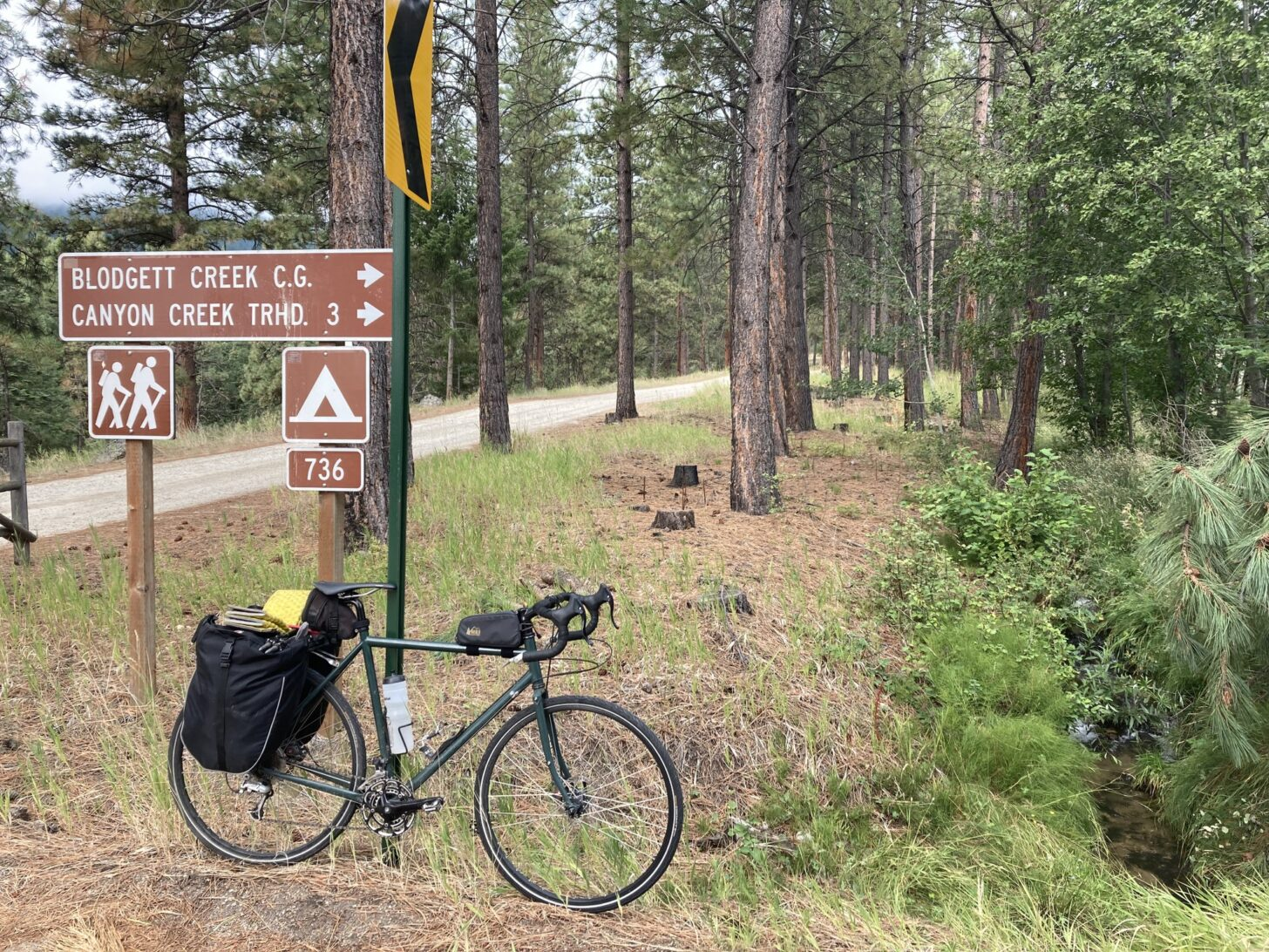 a road bike loaded down with backpacking gear leans up against a road sign pointing the way towards a trailhead